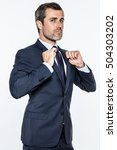 Small photo of ambitious young bearded businessman expressing pride, power, success with attitude and superiority with his hands checking his suit, isolated over white background