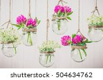 flowers in jars on a string. | Shutterstock . vector #504634762