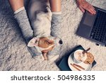 Stock photo woman in cozy home wear relaxing at home with sleeping dog jack russel terrier drinking cacao 504986335