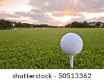 golf ball on tee of florida tropical course at dawn - stock photo