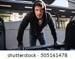 Criminal young man in black hoodie and gloves standing and looking at car trunk - stock photo