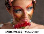 girl with butterfly make-up on face and flower look right - stock photo