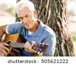 Senior Man Plying Guitar...