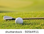 golf ball and iron club rest on fairway against morning backlit sunshine of florida course, focus on ball - stock photo