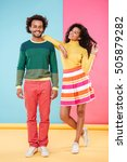 Small photo of Cheerful carefree african young couple standing and flirting over colorful background