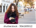 Small photo of young shopper woman taking out money from wallet on street