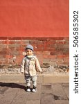 Small photo of BEIJING-OCT. 23, 2016. Cute little Chinese boy against ancient red wall. October 2015, China decided to overturn its decades-old one-child policy, allow couples across the country have two children.
