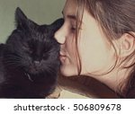 Stock photo little girl hugging and kissing a black kitten maine coon 506809678