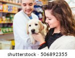 Stock photo young woman with her labrador retriever puppy at veterinary 506892355