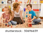 Family building with wooden blocks together sitting on the floor having fun - stock photo
