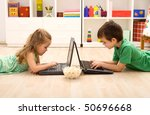 Kids with laptops and a bowl of popcorn playing on the floor - stock photo
