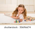 Little girl playing with wooden alphabetic blocks on the floor - stock photo