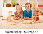 Happy kids with wooden blocks on the floor in their room - stock photo