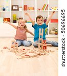 Kids proudly showing their wooden block buildings, sitting on the floor - stock photo