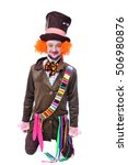 Small photo of The insane funny Hatter: a man dressed in a velour brown frock coat, cylinder hat and the bow tie kneeling and grimacing and is playing the fool - portrait, isolated