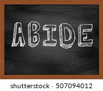 Small photo of ABIDE hand writing chalk text on black chalkboard