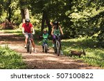 Family Biking In Forest With...