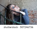 Small photo of Curly young woman aggressively holding staircase ragged lattice