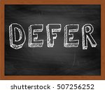 Small photo of DEFER hand writing chalk text on black chalkboard