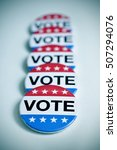 Small photo of some aligned badges with the word vote written in it, for the United States election, with a slight vignette added