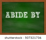 Small photo of ABIDE BY handwritten text on green chalkboard