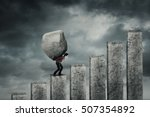 Small photo of Young businessman walking on the financial chart while carrying a big stone. Concept of hard work