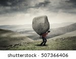 Small photo of Young businessman walking on the hill while carrying a big rock. Concept of business adversity