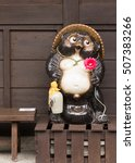 Small photo of Takayama, Japan - September 24, 2016: The legendary Tanuki statue holds red flower and the customary Sake flask. On brown wooden stand and brown background.