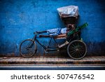 Small photo of DELHI, INDIA - SEPTEMBER 11, 2011: Indian cycle rickshaw driver sleeps on his bicycle in street of New Delhi. Cycle rickshaws are used in India from about 1930 and now common in rural and urban areas.