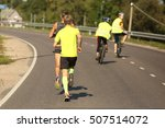 Small photo of runners at the city race with accompanying cyclist