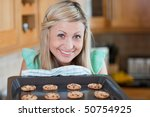 Cute Young Woman Baking Cookie...