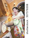 Small photo of Woman burning a meal in her kitchen, clumsy housewife set fire to her lunch