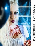 Small photo of Art portrait of a bloody girl. Halloween style make up. Girl with a knife. Maniac girl in cold blue room. Psychic Alice in wonderland.