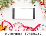 Small photo of Smartphone with blank screen in Christmas frame, mockup. New year trumpery and empty smartphone on white background, copy space for text or advertisement, void