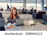 Small photo of Everything looks great. Beautiful young woman using laptop and notebook while sitting in waiting hall at airport