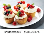 Tasty cupcakes with berries on grey table