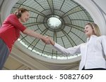 two women shaking hands under... | Shutterstock . vector #50827609