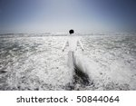 Small photo of Man walking into sea, being washed by waves, back view