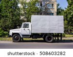 Small photo of old soviet russian freight car against green trees grass and house, grey white freight car side view