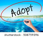 Small photo of Woman Hand Writing Adopt on blank transparent board with a marker isolated over water background. Business concept. Stock Photo