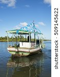Small photo of Colorful Brazilian fishing boat with tassels celebrating Yemanja, the goddess of the seas anchored in shallow water off the coast of Bahia Nordeste Brazil