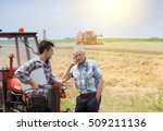 two farmers leaning on tractor... | Shutterstock . vector #509211136