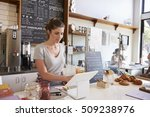 Woman Working On The Till At A...