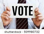 Small photo of Vote. Election concept. Man holding a card with message text.
