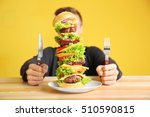 man eating huge burger at table | Shutterstock . vector #510590815