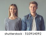Stock photo beautiful couple is looking at each other and smiling while standing straight on gray background 510914092
