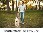 Stock photo handsome man walking his dog in the park 511247272