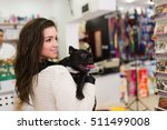 Stock photo beautiful brunette woman with her french bulldog puppy in pet shop selective focus on dog 511499008