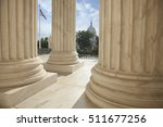 Small photo of Close up of the columns of the Supreme Court building with an American flag and the US Capitol in the background