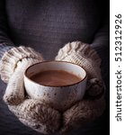 Small photo of Woman in mittens holding a cup of hot chocolate. Selective focus
